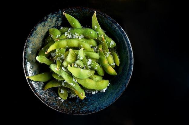 枝豆の海塩サラダをダークボウルでお召し上がりいただけます。黒いテーブルに隔離。レストランの食べ物。日本のキッチン