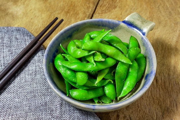 Edamame nibbles, boiled green soybeans, japanese food, top view on wooden table