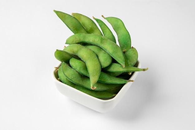 Японская кухня свежие на пару edamame или зеленые соевые бобы в белой миске на белой поверхности.