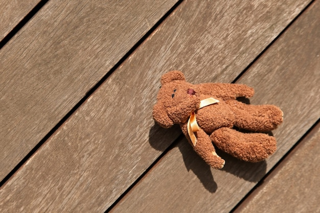 Eddy bear left on the wooden porch, top view