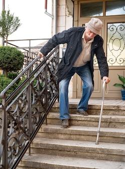 杖を持った防毒マスクを着た老人が屋外の階段を降りる