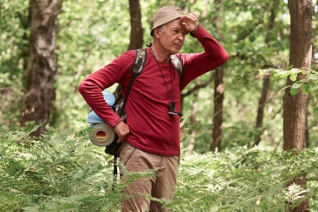 Edery искатель приключений с рюкзаком и ковриком стоит в лесу, уставший, держит руку на лбу, обтягивая коричневые повседневные брюки