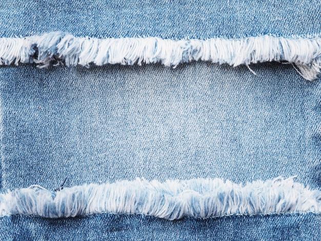 Рамка края голубой джинсовой ткани сорванная над предпосылкой текстуры джинсов.
