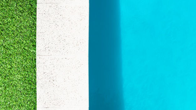 Edge of grass, stone border and water of pool