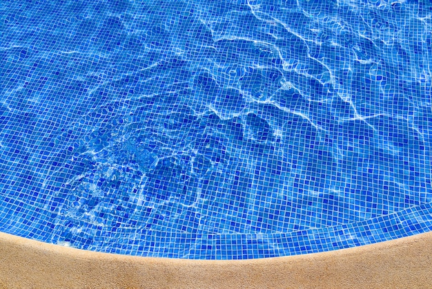 The edge of the round blue swimming pool and the shiny clear water. top view.