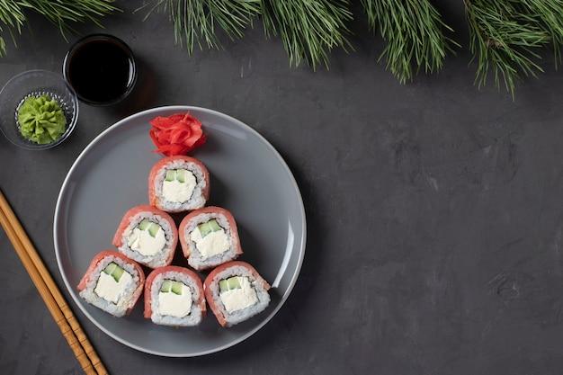 灰色のプレートにフィラデルフィアチーズを添えたマグロの寿司から作られた食用のクリスマスツリー。新年会。テキスト用のスペース。上面図