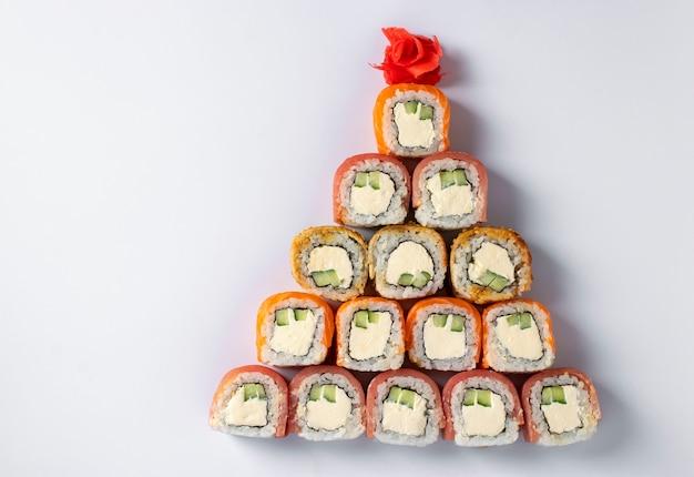 Съедобная рождественская елка из суши с лососем, тунцом и угрем с сыром филадельфия на белом. новогодняя вечеринка. место для текста. вид сверху