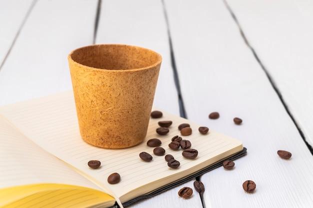 Съедобная кофейная чашка с жареными бобами на белом фоне образ жизни без отходов концепции