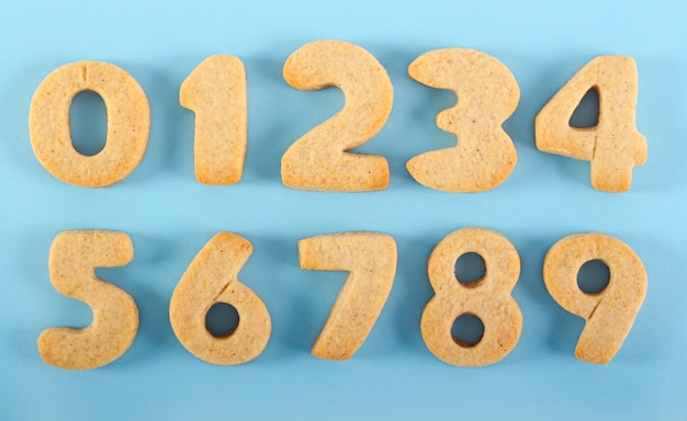 Edible handmade numbers cookies over blue background