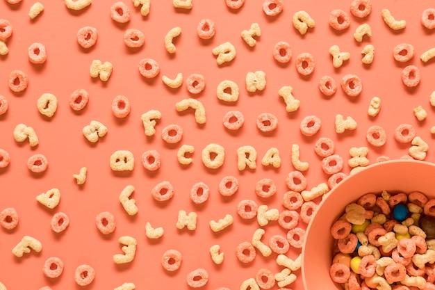 Съедобные буквы алфавита и чаши на оранжевом фоне