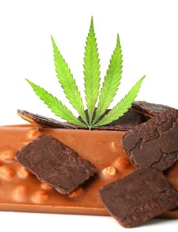 Edible medical marijuana food chocolate bars and chocolate cookies with green hemp leaf isolated