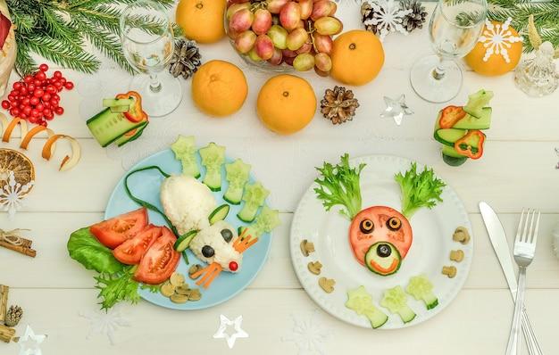 新年とクリスマスのお祝いのテーブルのための野菜で作られた食用ネズミと食用鹿