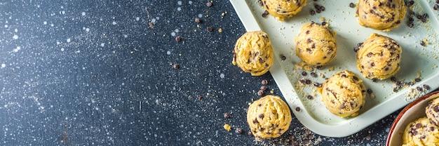 식용 생 반죽. 미국 디저트, 초콜릿 방울을 넣은 식용 생 쿠키 반죽, 작은 그릇과 베이킹 시트, 짙은 파란색 배경 복사 공간