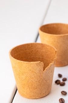 Съедобные вафельные кофейные чашки с жареными кофейными зернами на белом деревянном столе, концепция нулевых отходов