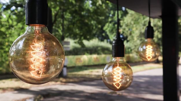 エジソンの白熱電球はレトロなロフトスタイルでぶら下がっています。食堂の装飾のクローズアップ。街路装飾ライトランタン暖かい光。ソフトフォーカス、ぼやけた通りの背景。