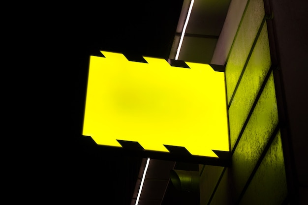 Editable psd mockup with hanging outdoor glowing sign board at night.