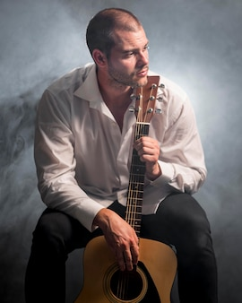 Edited photo of man and acoustic guitar in the smoke
