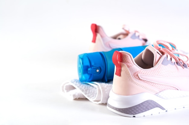 Editorial, fitness equipment, sport background. sneakers, towel, and bottle of water. background with copy space.