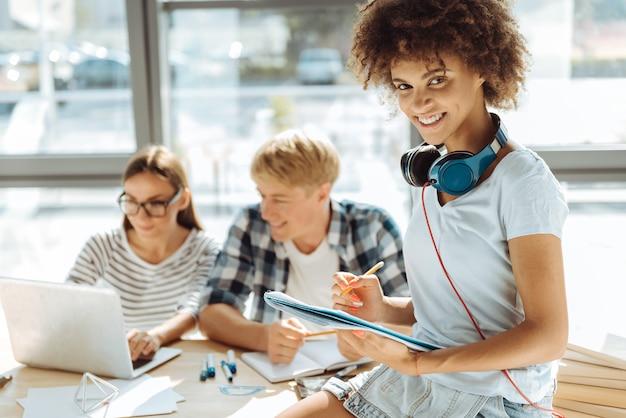 교육받은 세대. 긍정적 인 미소 젊은 아프리카 계 미국인 여자 노트를 만들고 백그라운드에서 공부하는 그녀의 groupmates 동안 헤드폰을 사용