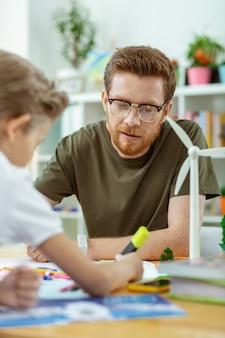 어린 소년을 교육합니다. 열심히 일하는 학생들과 포스터 작업에 집중된 잘 생긴 생강 교사