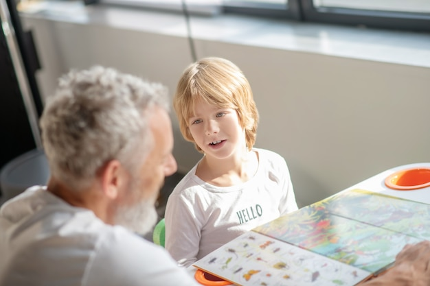 教育。父親と一緒に本を読みながら動物種を学ぶ少年