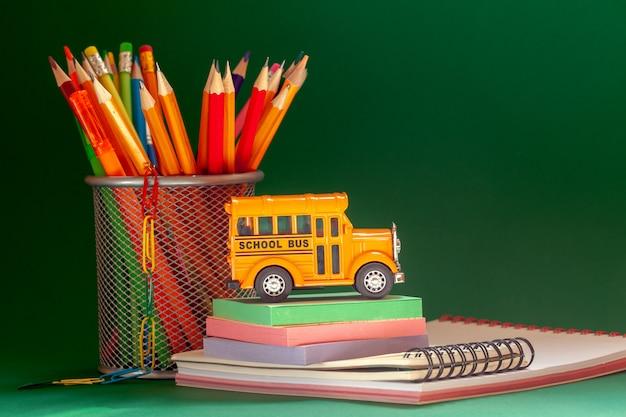 教育と学校のコンセプトに戻る。黄色のレトロなスクールバスと鉛筆のバスケット、ダークグリーンの教科書
