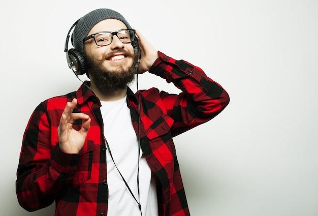 教育と人々の概念。灰色の上に立って音楽を聴いている若いひげを生やした男