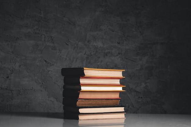 Концепция образования и чтения - группа красочных книг на белом столе на сером фоне