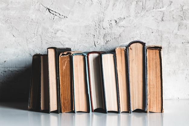 Концепция образования и чтения, группа старых красочных книг на белом столе на сером фоне