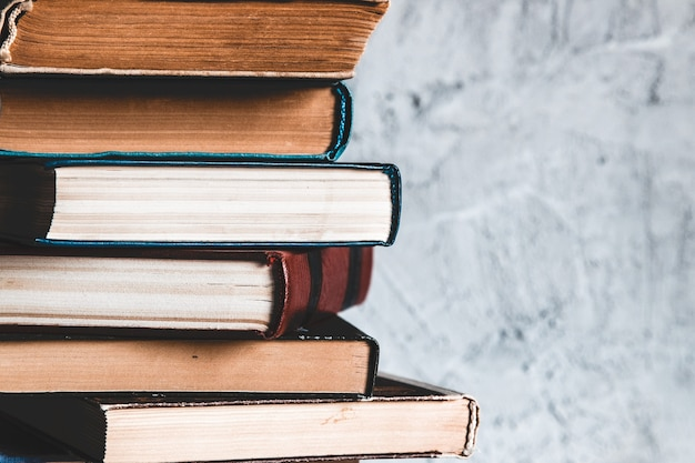 교육 및 독서 개념, 회색 배경에 흰색 테이블에 오래 된 다채로운 책의 그룹