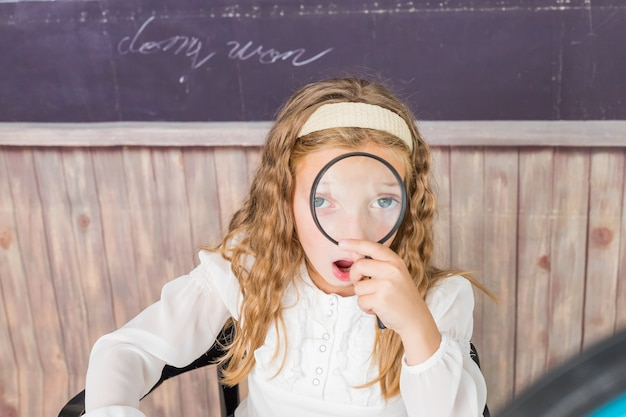 Концепция образования и школы маленькая девочка с лупой в школе школьница сидит в классе ...