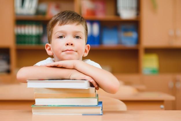 Концепция образования и школы - улыбающийся маленький мальчик с множеством книг в школе