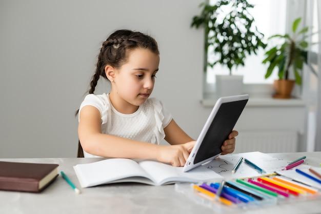 Концепция образования и школы - улыбающаяся маленькая девочка студента с множеством книг в школе.