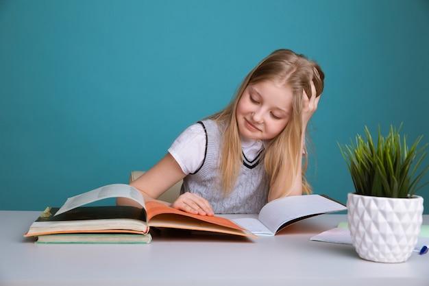 Концепция образования и школы - улыбающаяся маленькая девочка студента с множеством книг в школе