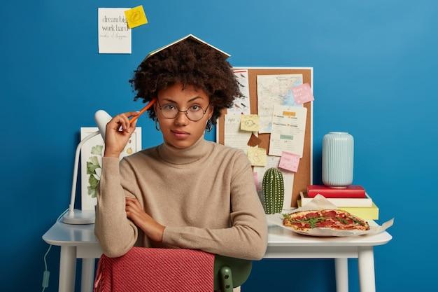 Концепция образования и обучения. задумчивая женщина с вьющимися волосами, блокнотом на голове, держит ручку возле виска, думает, о чем написать, носит большие круглые очки