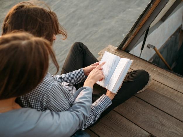 教育と勉強。新しい情報を学ぶためのリラックスした方法。学生たちは屋上で本を読む