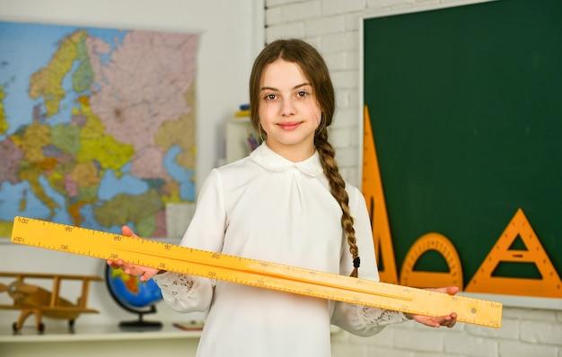 教育と大学。女子高生は定規を保持します。測定器。さまざまな学校の要素。秋の学校時代の文房具。学校に戻る。大学での教育。幾何学に夢中。
