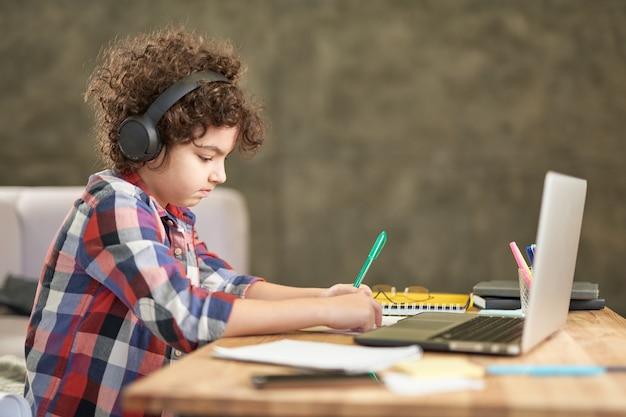 Обучение на расстоянии восторженный латиноамериканский мальчик в наушниках выглядит сосредоточенным, пока
