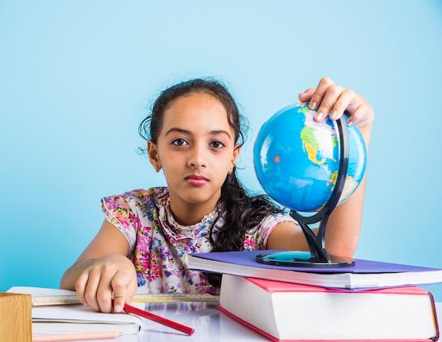 家庭での教育の概念-本の山、教育地球儀などで自宅で勉強しているかわいい小さなインドまたはアジアの女の子。選択的な焦点