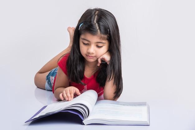 自宅での教育のコンセプト-自宅の床に座って本とコーヒーマグの山で勉強しているかわいい小さなインドまたはアジアの女の子。白い背景の上に分離