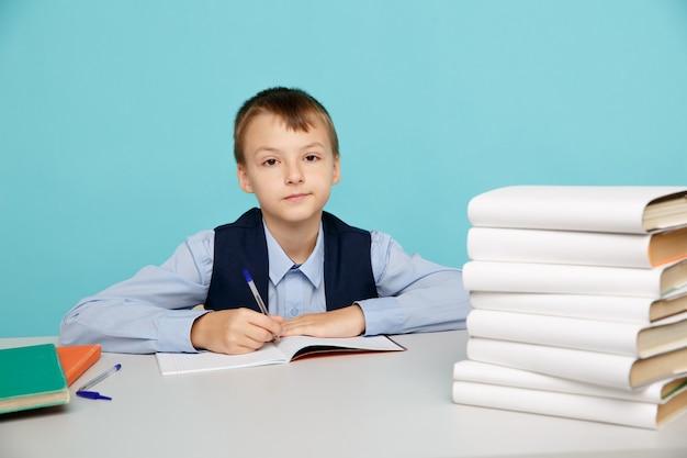 학교 개념에서 교육. 테이블에 앉아 공부 하 고 고립 된 소년입니다.