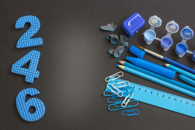 Education or back to school . blue school supplies on blackboard with copyspace.