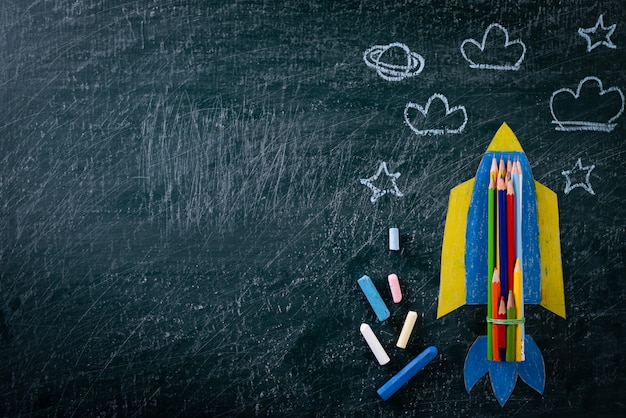 Education or back to school concept. painted paper rocket on chalkboard