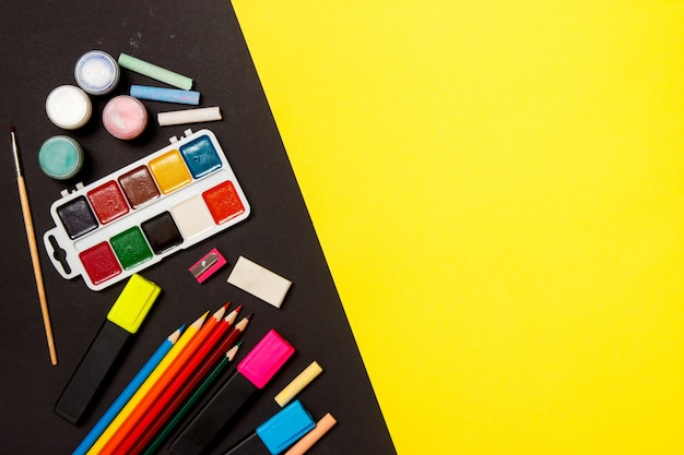 Education and back to school concept. school supplies for drawing on a yellow background. top view, flat lay.