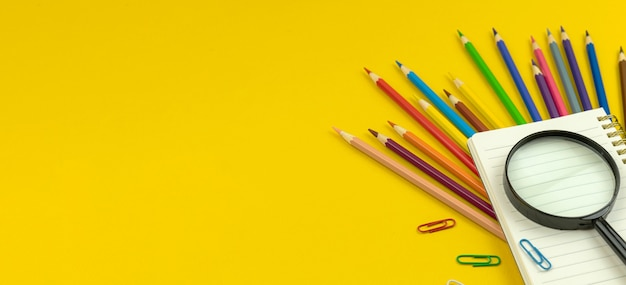 Education banner, back to school concept, yellow desktop with color pencils, notepad and magnifying glass, copy space photo
