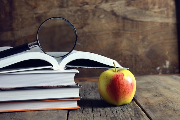Education book apple and magnifying glass