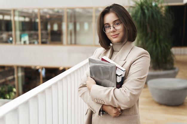 教育、ビジネス、女性のコンセプト。若い魅力的でエレガントな女性家庭教師、若い教師または学生の肖像画は、カメラを笑顔でホールに立って、勉強の本やノートパソコンを運びます。