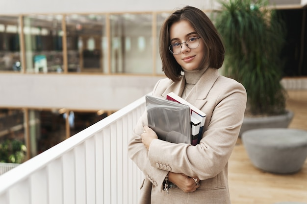 Education, business and women concept. portrait of young attractive, elegant female tutor, young teacher or student carry studying books and laptop, standing in hall smiling camera.