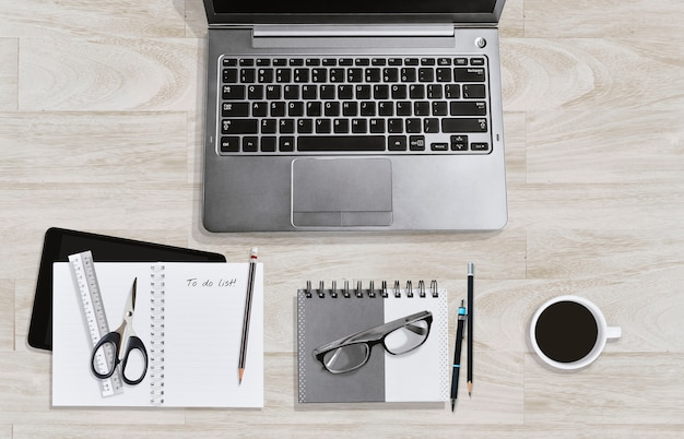 Education or business workspace concept, notebook, laptop and accessories eyeglasses and coffee cup