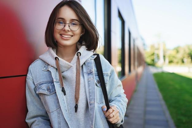 Концепция образования, карьеры и людей. крупным планом портрет успешной симпатичной молодой женщины, изучающей ит, голову в коворкинг, чтобы заняться внештатной работой, улыбаясь счастливой камерой, стоять на улице
